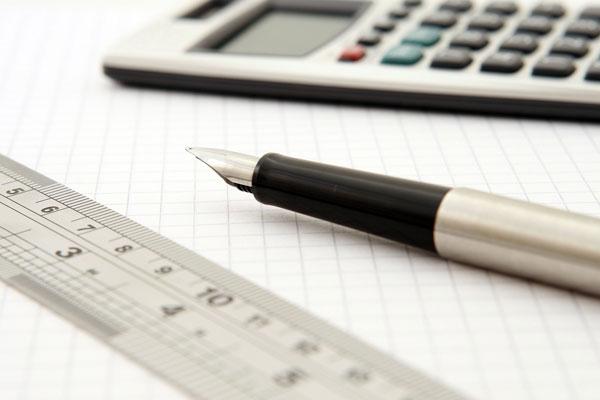 Taschenrechner, Stift, Lineal auf karierten Blatt