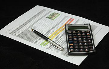 Energieausweis mit Stift und Taschenrechner