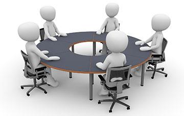 Männchen sitzen an rundem Tisch