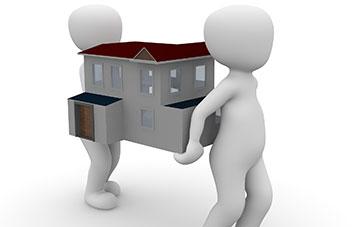 Zwei Männchen tragen ein Haus