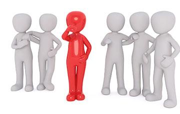 Fünf weiße Männchen mit einem roten Männchen