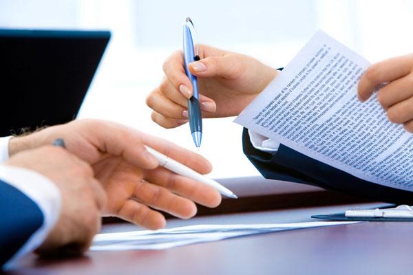 zwei Hände halten Kugelschreiber und Vertrag